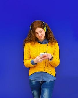 Chica escuchando música en auriculares con smartphone