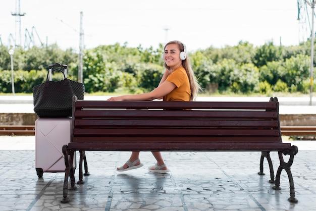 Chica escuchando música en un banco en la estación de tren