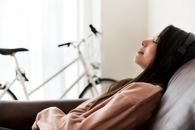 Chica escuchando música en casa en el sofá