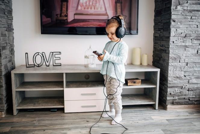 Chica escuchando música cerca de la televisión
