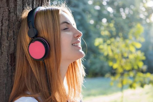 Chica escuchando música en grandes auriculares rosados