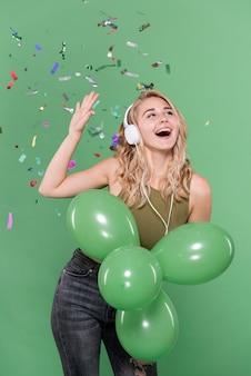 Chica escuchando música y sosteniendo globos