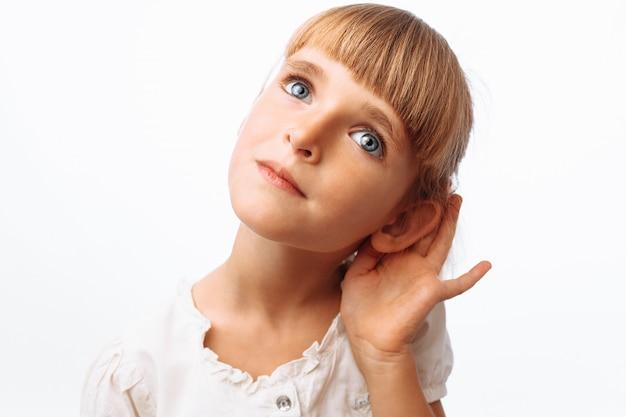 Chica escuchando en la pared blanca