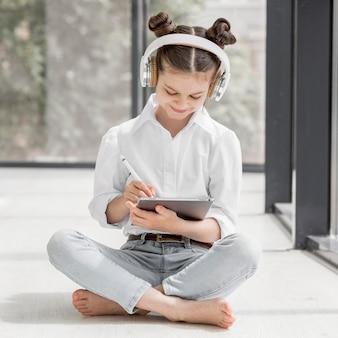 Chica escuchando a su maestra a través de auriculares