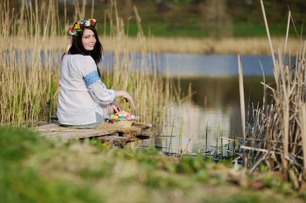 Chica eslava en camisa ucraniana sentada en el puente con pascua
