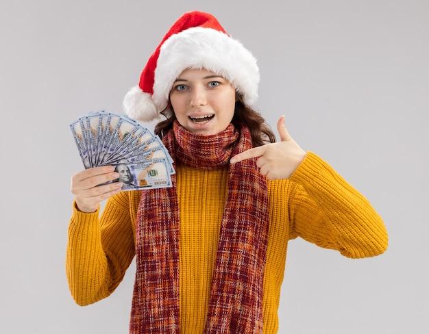 Chica eslava joven sorprendida con sombrero de santa y con bufanda alrededor del cuello sosteniendo y apuntando al dinero aislado en la pared blanca con espacio de copia