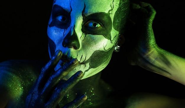 Chica espeluznante atractiva con maquillaje esqueleto