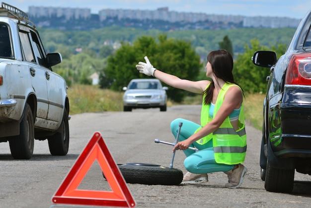 Chica esperando ayuda con el reemplazo de la rueda de repuesto