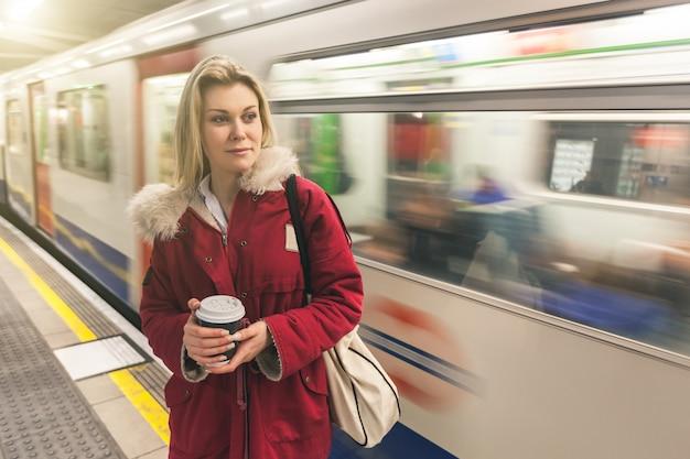 Chica esperando el tren en la estación