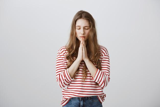 Chica esperanzada cogidos de la mano en oración, suplicando