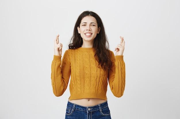 Chica esperanzada cruzar los dedos y pedir deseos