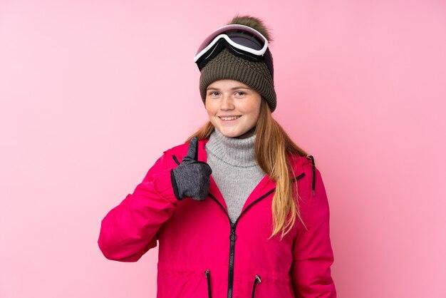 Chica esquiador adolescente con gafas de snowboard dando un gesto de pulgares arriba