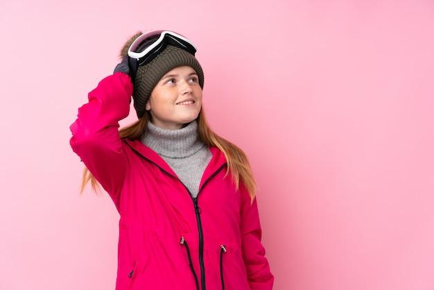 Chica esquiador adolescente ucraniano con gafas de snowboard sobre risa rosa aislado