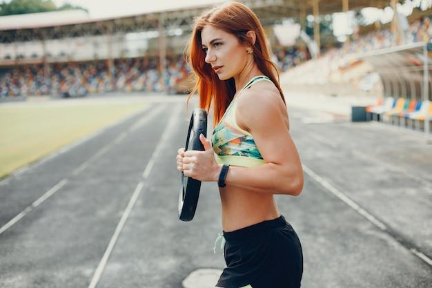 La chica en el estadio está jugando deportes.