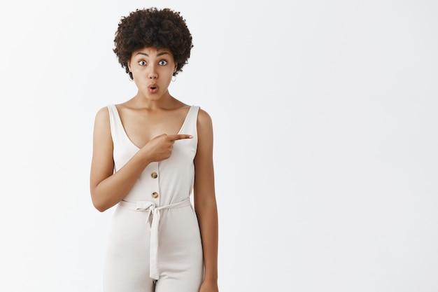 Chica con estilo alegre posando contra la pared blanca