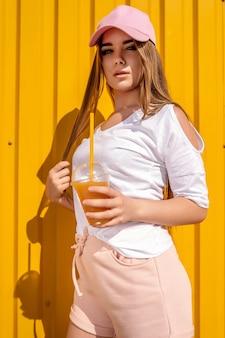Chica de estilo hipster bastante joven divertirse al aire libre con gorra blanca y comer helado en amarillo