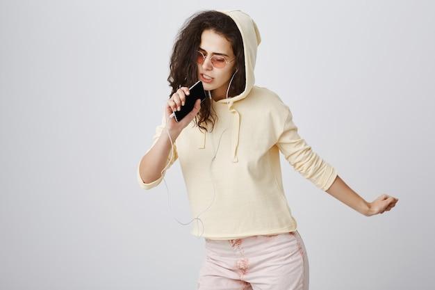 Chica con estilo jugando aplicación de karaoke, cantando canciones en el teléfono móvil, usando auriculares