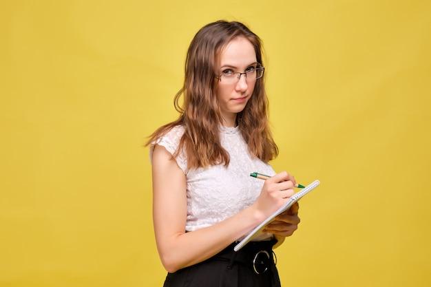 Chica estricta maestra con gafas sobre un fondo amarillo hace una nota con un bolígrafo en un cuaderno.