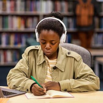 Chica estudiando en la biblioteca de la universidad