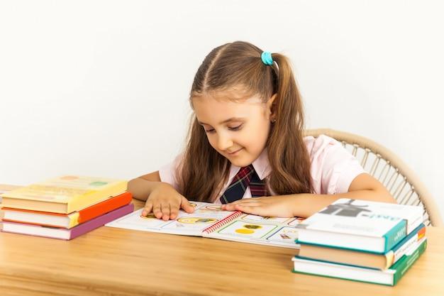 Chica estudiando en la mesa sobre fondo blanco.