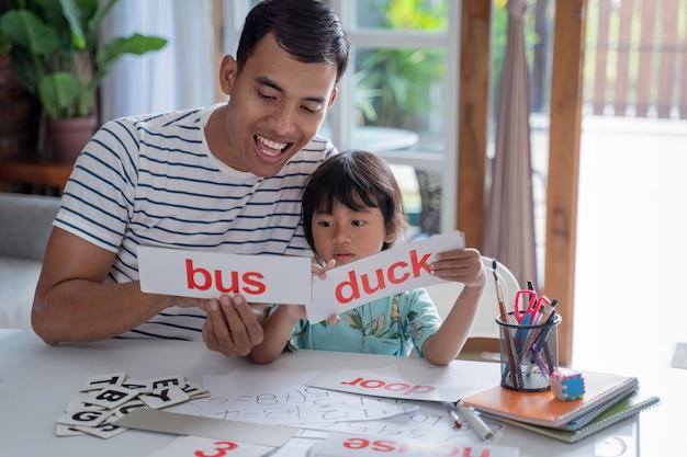 Chica estudiando palabras con el padre en casa