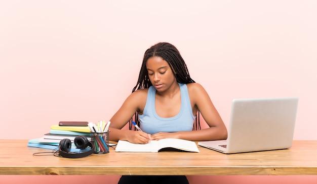 Chica estudiante adolescente afroamericana con cabello largo trenzado en su lugar de trabajo
