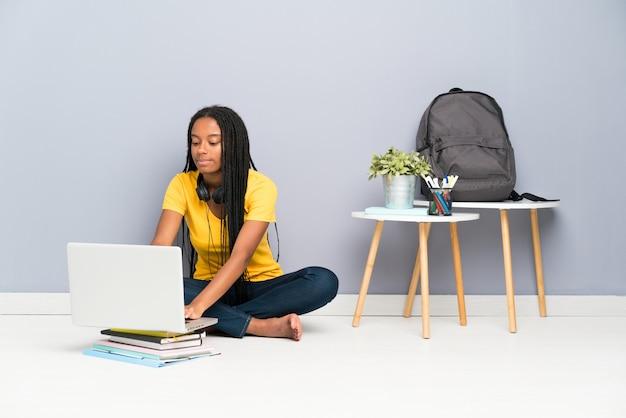 Chica estudiante adolescente afroamericana con largo cabello trenzado sentado en el piso