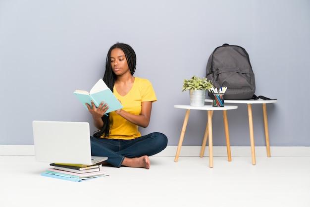 Chica estudiante adolescente afroamericana con largo cabello trenzado sentado en el suelo y leyendo un libro