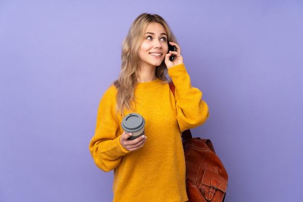 Chica estudiante adolescente aislada en la pared púrpura con café para llevar y un móvil