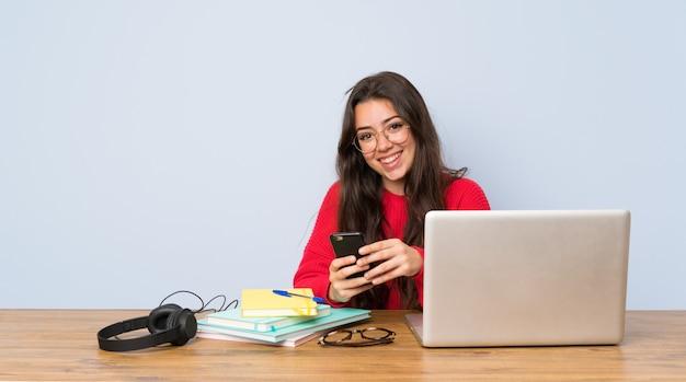 Chica estudiante adolescente estudiando en una mesa enviando un mensaje con el móvil