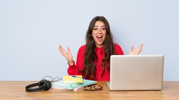 Chica estudiante adolescente estudiando en una mesa con expresión facial sorprendida