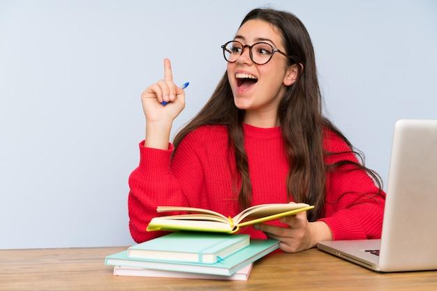 Chica estudiante adolescente estudiando en una mesa pensando