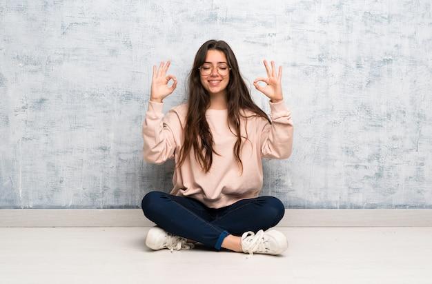 Chica estudiante adolescente estudiando en una mesa en pose zen