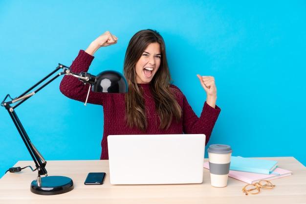 Chica estudiante adolescente en un lugar de trabajo sobre pared azul
