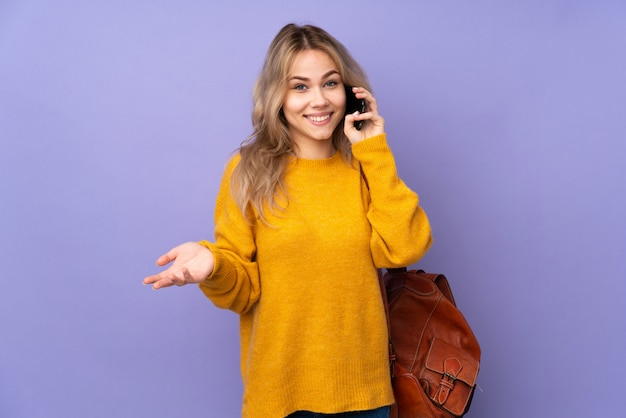 Chica estudiante adolescente en pared púrpura manteniendo una conversación con el teléfono móvil con alguien