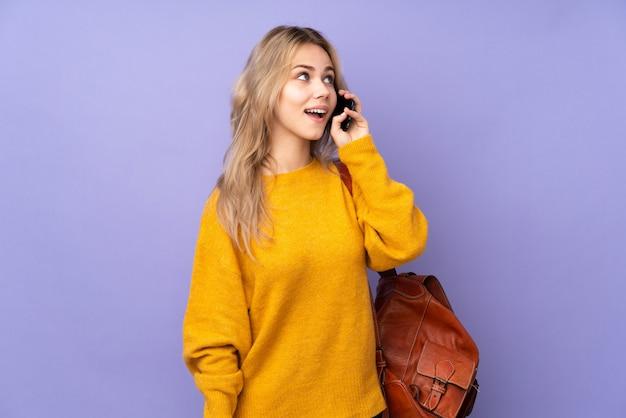 Chica estudiante adolescente en pared púrpura manteniendo una conversación con el teléfono móvil