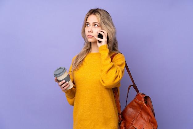 Chica estudiante adolescente en púrpura con café para llevar y un móvil