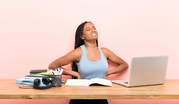 Chica estudiante adolescente que sufre de dolor de espalda por haber hecho un esfuerzo