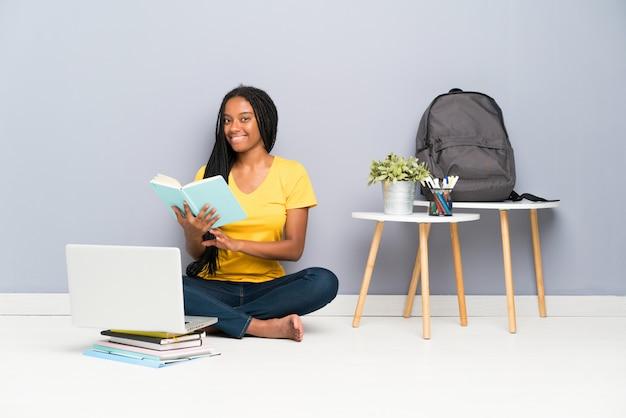 Chica estudiante adolescente sentada en el suelo y leyendo un libro