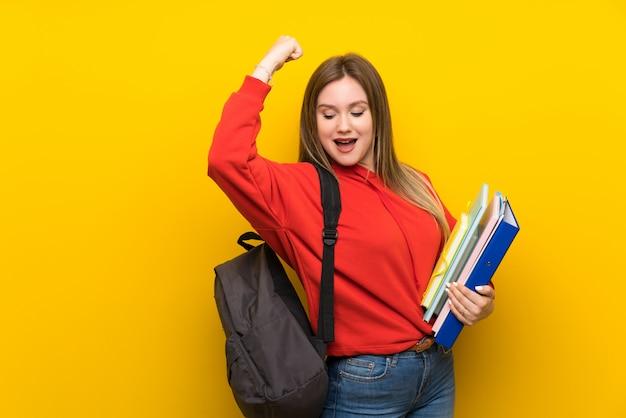 Chica estudiante adolescente sobre amarillo celebrando una victoria