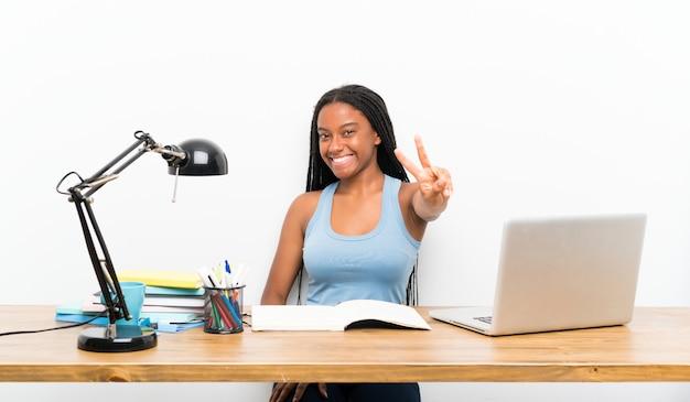 Chica estudiante adolescente sonriendo y mostrando el signo de la victoria