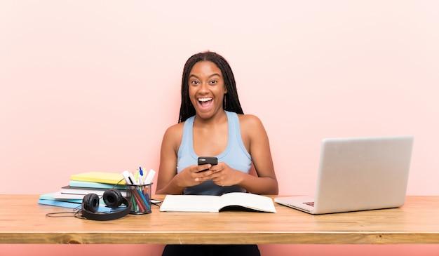 Chica estudiante adolescente sorprendida y enviando un mensaje