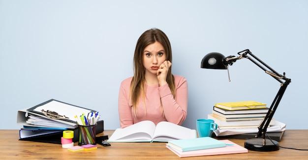 Chica estudiante adolescente en su habitación nerviosa y asustada.