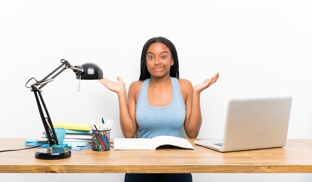 Chica estudiante adolescente teniendo dudas mientras levanta las manos