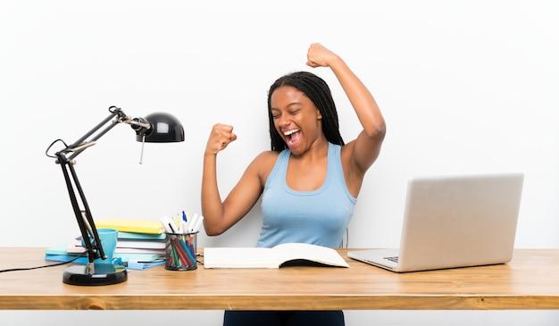 Chica estudiante afroamericana adolescente con cabello largo trenzado en su lugar de trabajo celebrando una victoria