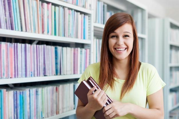 Chica estudiante alegre con libros