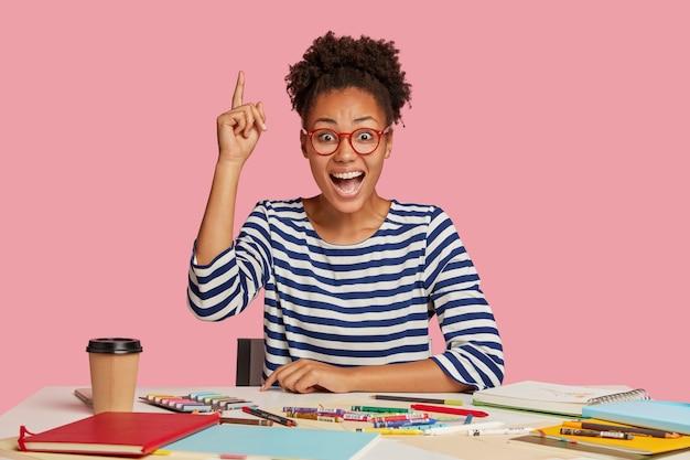 Chica estudiante alegre posando en el escritorio contra la pared rosa