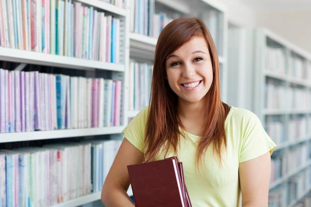Chica estudiante alegre sosteniendo libros en la biblioteca