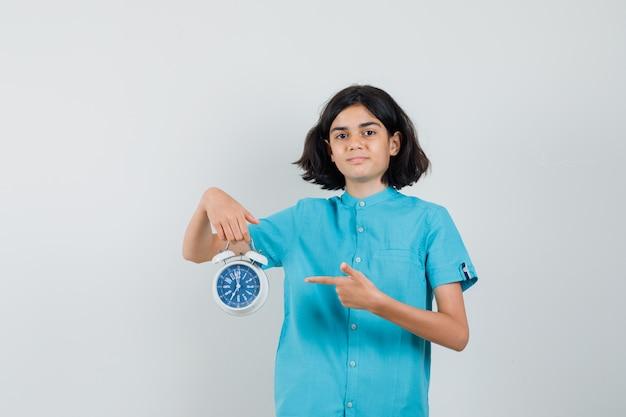 Chica estudiante en camisa azul apuntando al reloj y mirando seguro