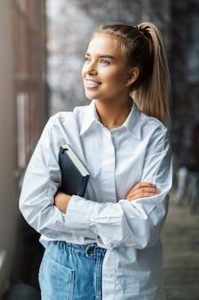 Chica estudiante en camisa blanca sonríe y se coloca junto a la ventana.
